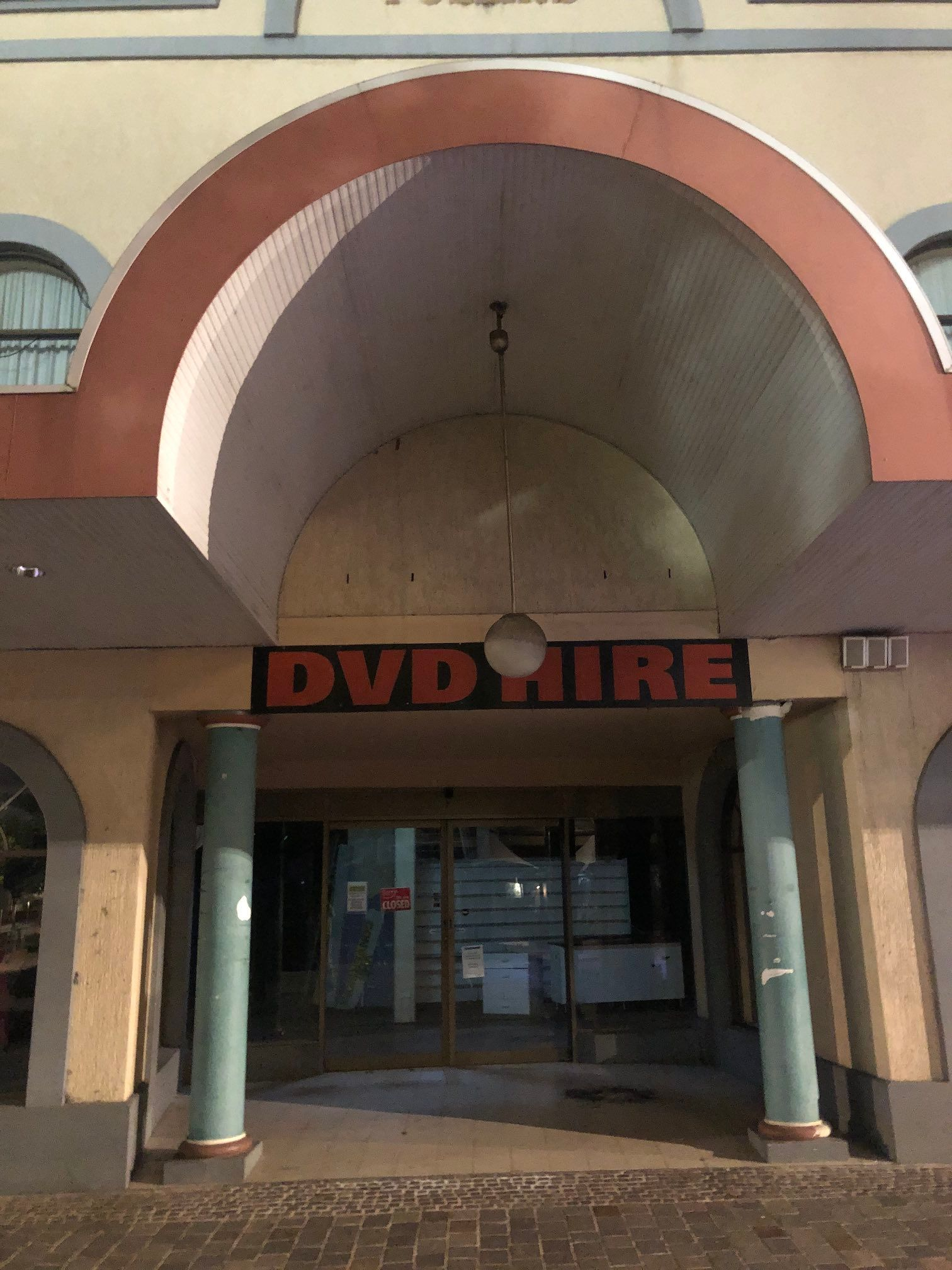 Ex-DVD Hire shop, now for lease, with columns and oversized arch above entrance.