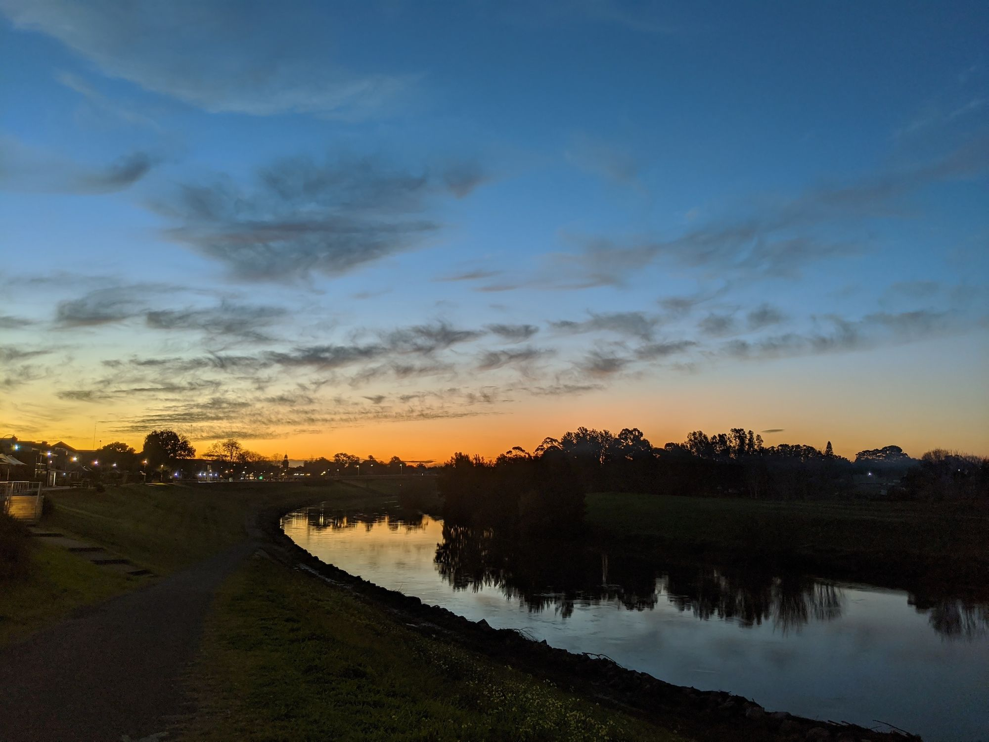 River foreground, sunset background, path on the left of the river.