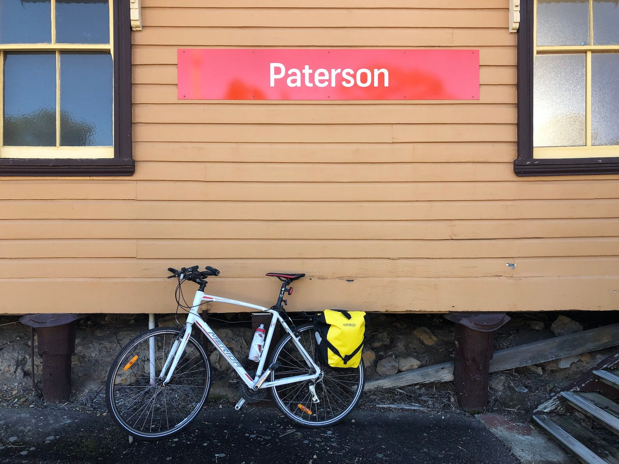 "Bicycle with panniers, in front of wooden train station building, labelled ""Paterson"""