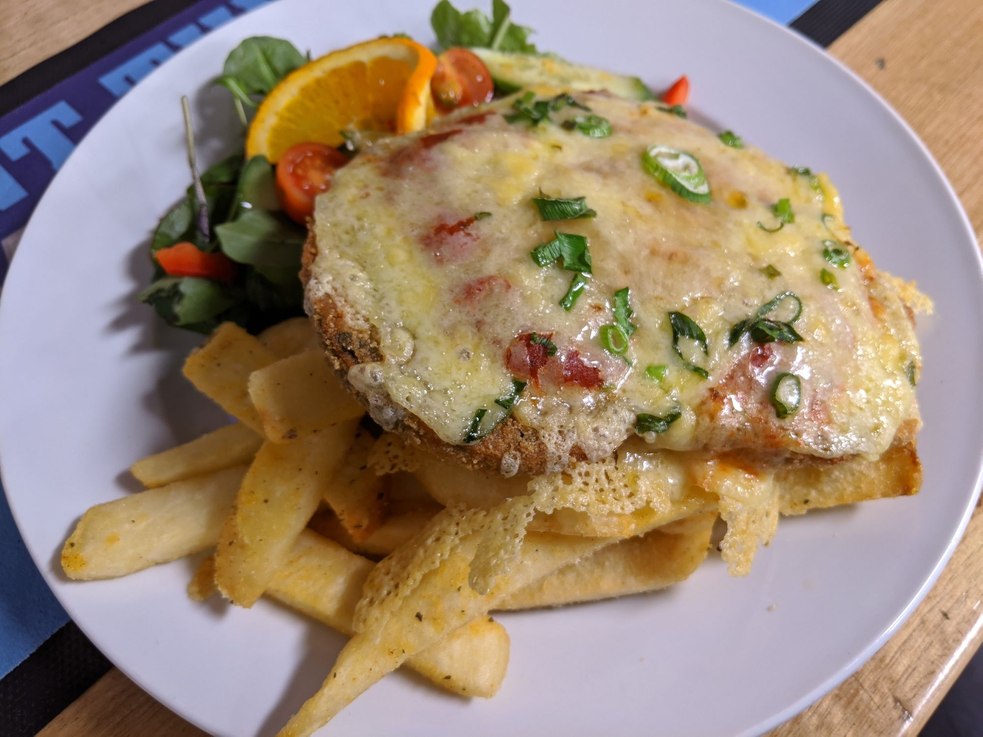 Vegetarian Parmigiana on plate with salad and chips.